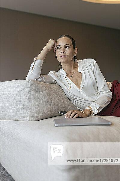Nachdenkliche reife Geschäftsfrau sitzt mit digitalem Tablet und Smartphone auf dem Sofa