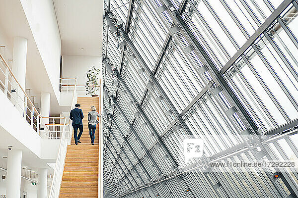 Business partners walking on staircase in office