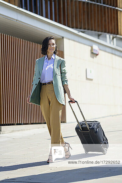 Smiling businesswoman walking with suitcase on footpath