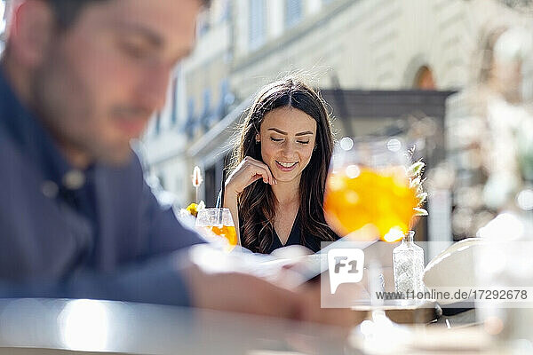 Young woman smiling at sidewalk cafe on sunny day