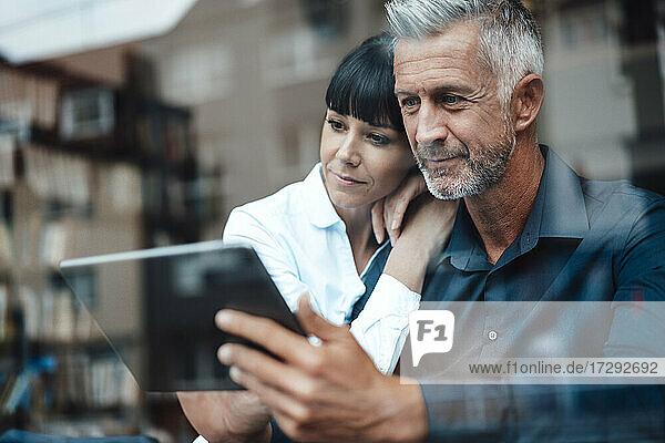 Geschäftspaar nutzt gemeinsam ein digitales Tablet in einem Café