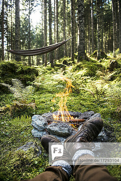 Shoes of man relaxing in front of stone campfire burning in forest