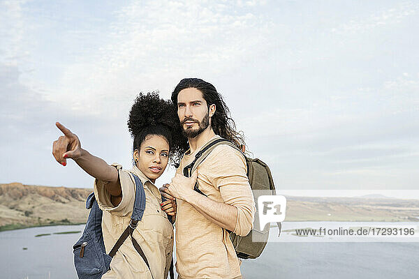 Girlfriend with backpack pointing while standing by boyfriend