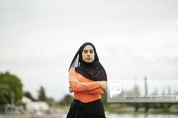 Arab woman wearing headscarf standing with arms crossed outdoors