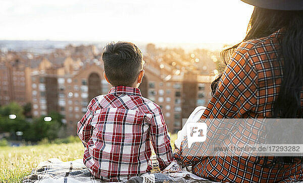 Mother and son looking at view while sitting on hill during sunset