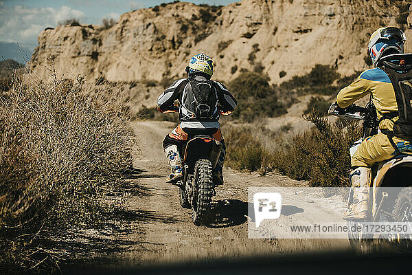 Male biker with protective sportswear riding motorcycles on desert road