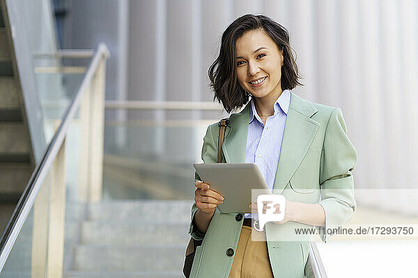 Smiling female professional with digital tablet in office building