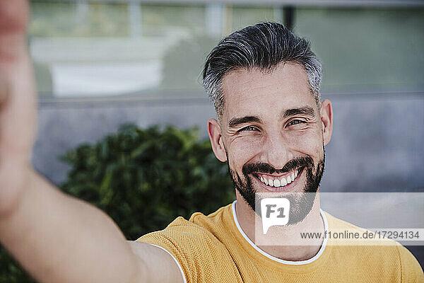 Smiling man taking selfie through smart phone