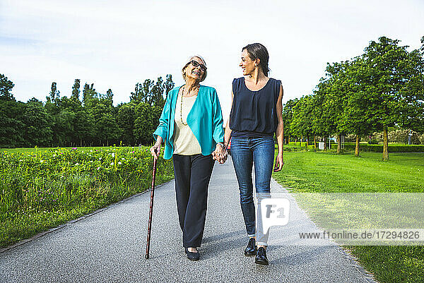 Smiling grandmother holding hand of granddaughter while walking on road