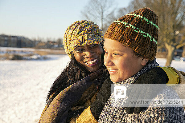 Smiling mature woman standing with arm around looking at son wearing knit hat