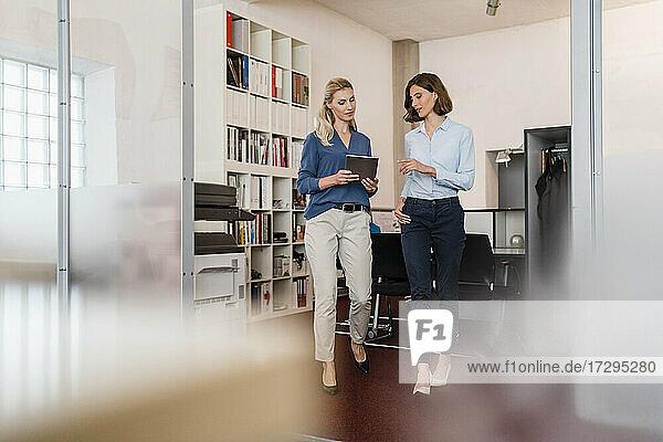 Unternehmerinnen diskutieren beim Gang ins Büro über ein digitales Tablet