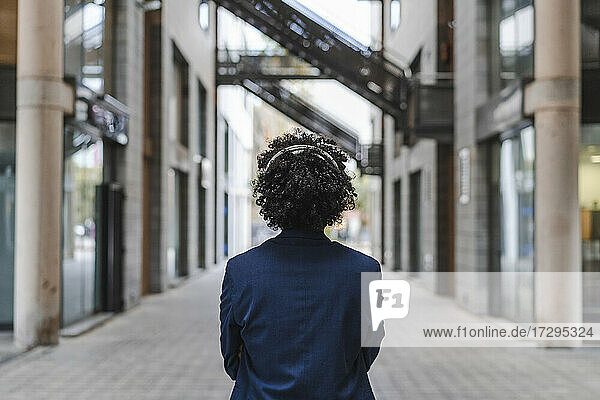 Businessman with headphones standing on footpath