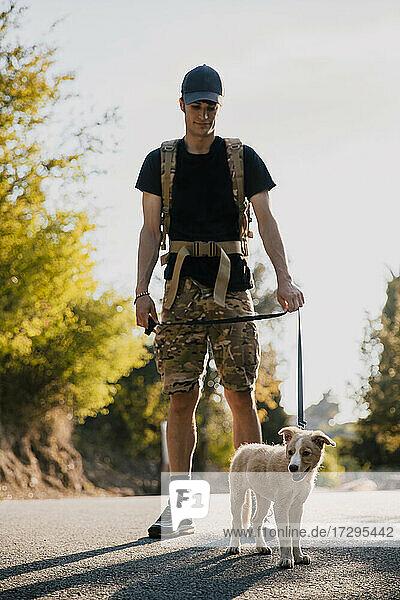 Junger Mann mit Rucksack steht mit Hund auf der Straße