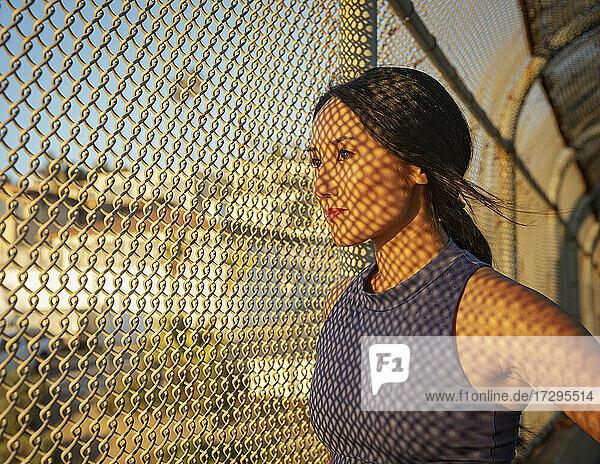 Sportlerin  die sich am Zaun ausruht