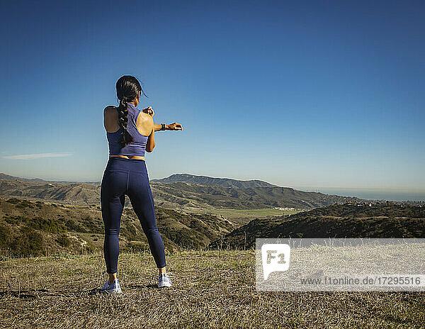 Rückansicht einer sich streckenden Frau in einer Landschaft