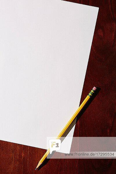 Draufsicht auf leeres Papier und Bleistift auf dem Schreibtisch