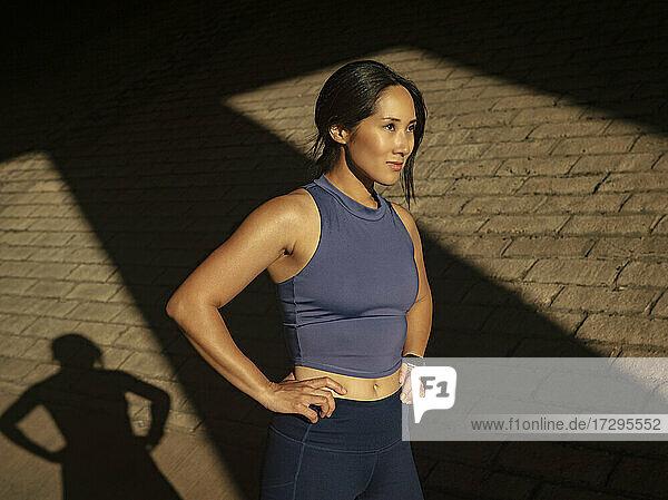 Frau in Sportkleidung in der Nähe einer Backsteinmauer im Sonnenlicht