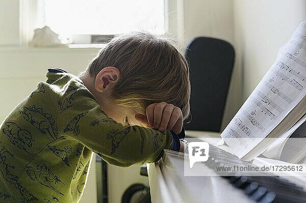 Trauriger Junge (6-7) lehnt am Klavier
