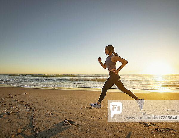 Frau joggt am Strand bei Sonnenuntergang