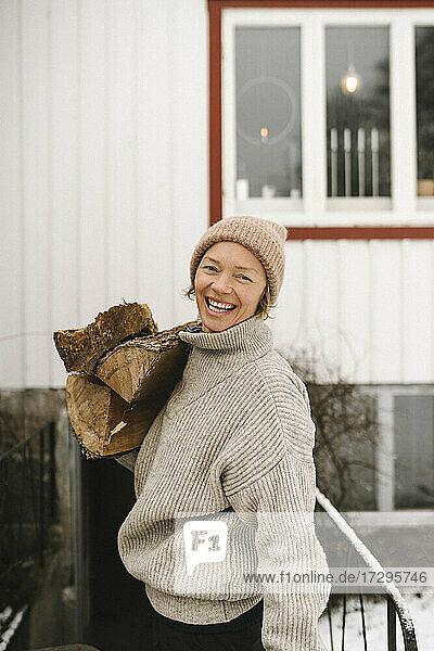 Porträt einer fröhlichen Frau  die im Winter Brennholz trägt