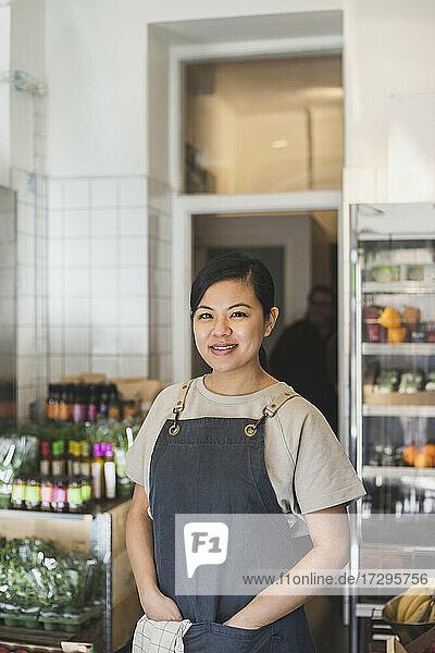 Porträt einer lächelnden Besitzerin mit Händen in den Taschen im Geschäft