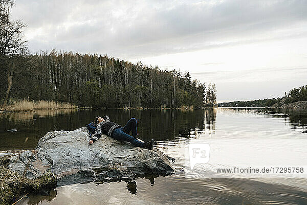 Female hiker resting on rock by lake against sky