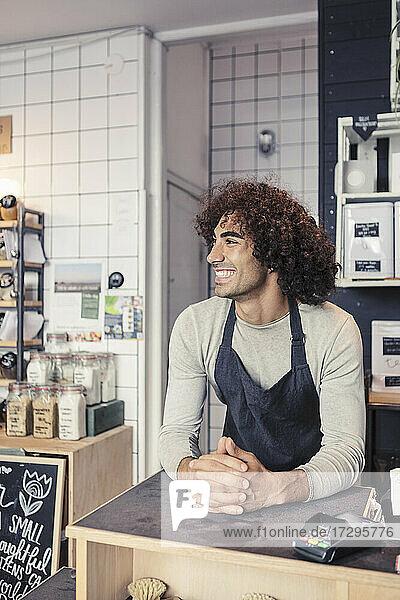 Lächelnder männlicher Unternehmer  der wegschaut  während er sich auf den Kassentisch lehnt