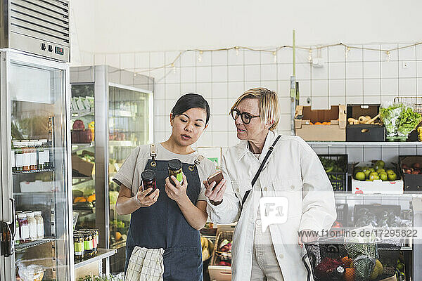 Female owner showing product to customer while buying in store