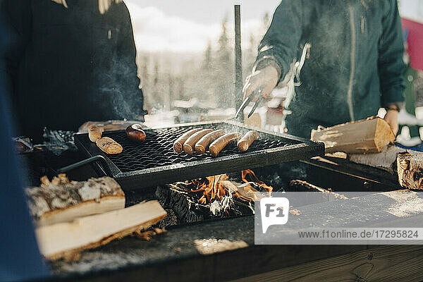 Midsection of friends preparing sausages on barbecue grill