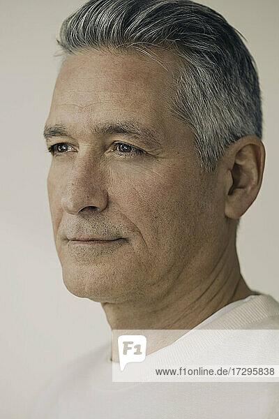 Älterer Mann mit grauen Haaren gegen beige Hintergrund