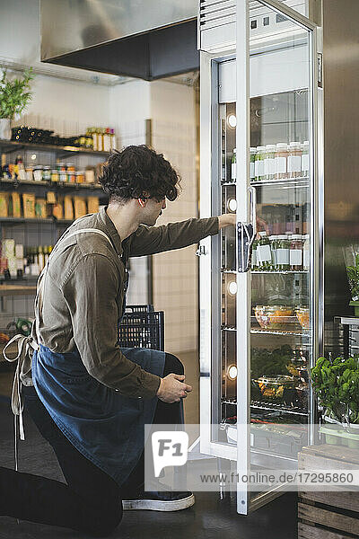 Young male owner taking bottle from refrigerator at store