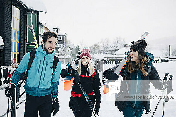 Happy male and female friends walking together during winter