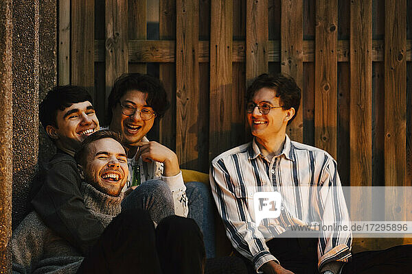 Cheerful multi-ethnic male friends spending leisure time in balcony
