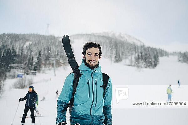 Portrait of smiling man standing at ski resort during winter