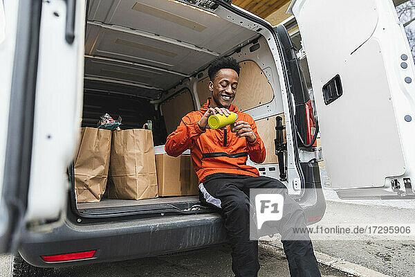 Happy männliche Lieferung Person gießen Kaffee  während in van Kofferraum sitzen