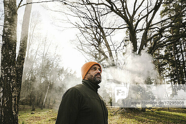 Mature male hiker exploring forest in foggy weather