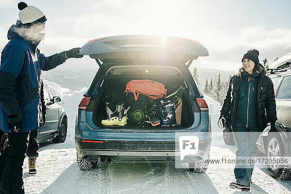 Lächelnde Frau  die einen männlichen Freund ansieht  während sie im Winter an einem sonnigen Tag beim Auto steht