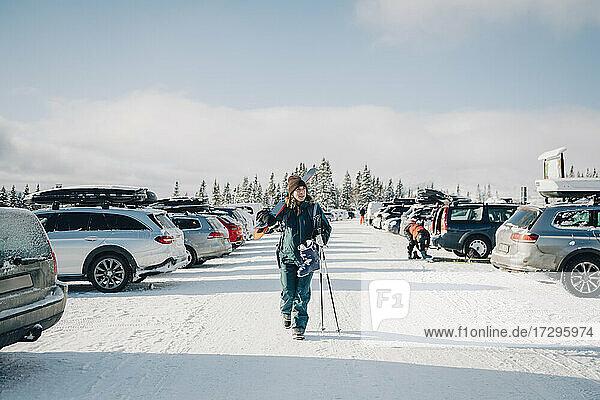 Volle Länge der Frau wegschauen  während zu Fuß inmitten von Autos auf dem Parkplatz gegen den Himmel