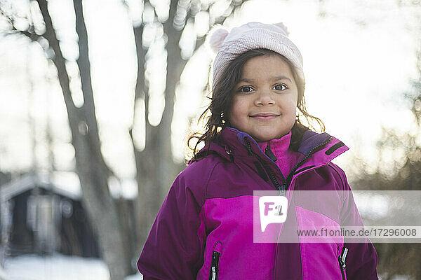 Porträt eines lächelnden Mädchens mit warmer Kleidung im Winter
