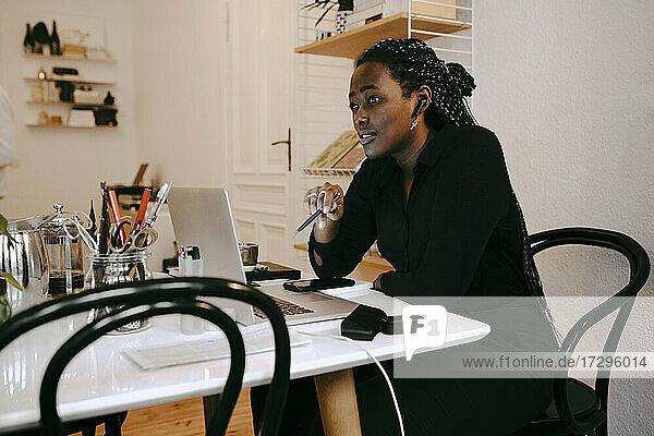 Weibliche Unternehmerin sitzt mit Laptop arbeiten im Home-Office