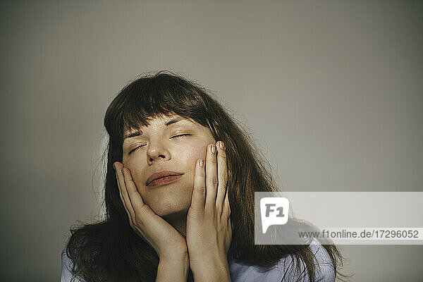 Young woman with eyes closed against white background