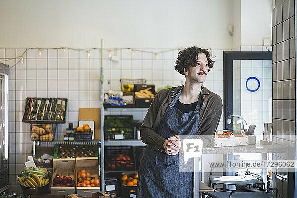 Männlicher Besitzer schaut weg  während er sich im Geschäft auf den Tisch stützt