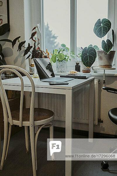 Laptop auf dem Tisch am Fenster im Heimbüro