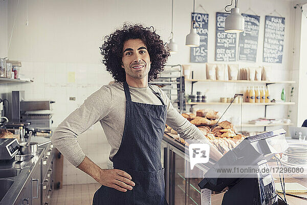 Portrait of male entrepreneur standing with hand on hip by cash register at checkout in cafe