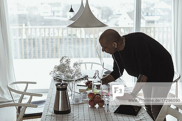 Male entrepreneur writing on adhesive note at table in living room
