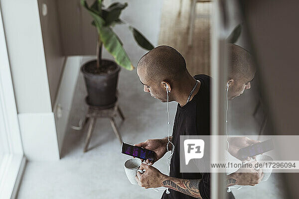 High angle view of man using smart phone while standing at home