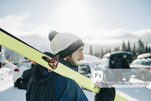 Bearded man with ski on sunny day during winter