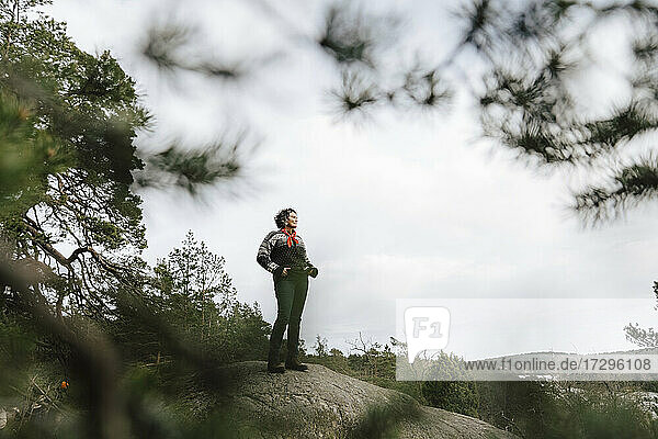 Female explorer standing on rock in forest