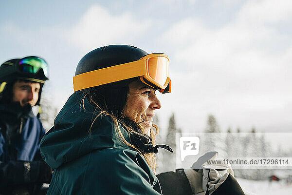 Lächelnde Frau trägt eine Skibrille und hält eine Kaffeetasse im Winter