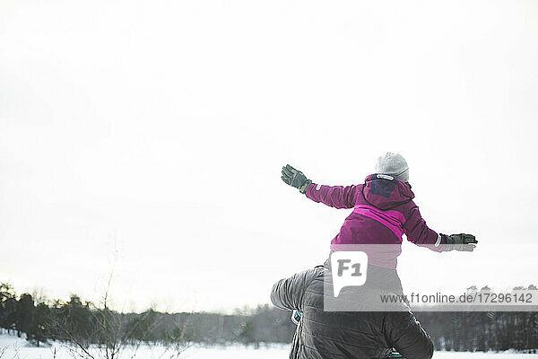 Rückansicht des Vaters  der seine Tochter im Winter auf den Schultern trägt